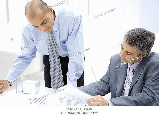 Two businessmen looking over documents together