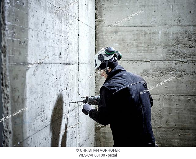 Construction worker drilling, electric drill