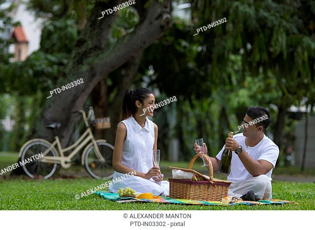 Singapore, Young couple having picnic with bicycle in background