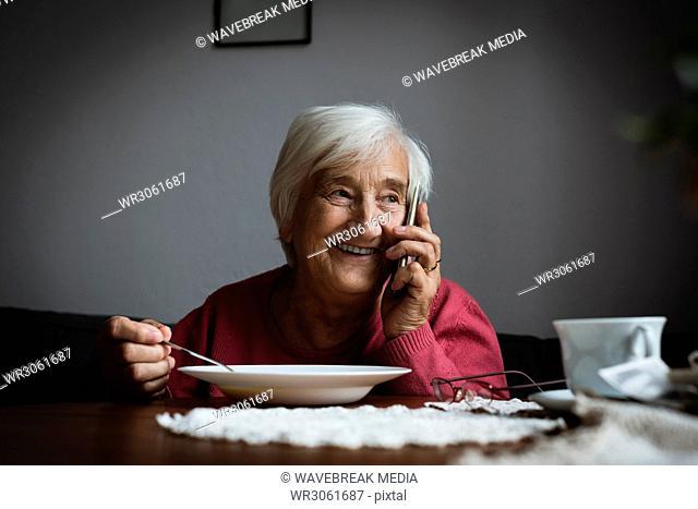 Senior woman talking on mobile phone while having breakfast