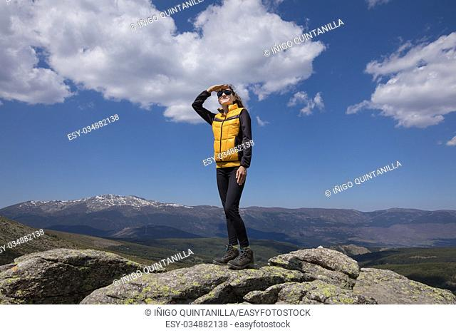 sport hiking or trekking woman with yellow and black clothes, standing on rock peak, with hand on face looking into distance