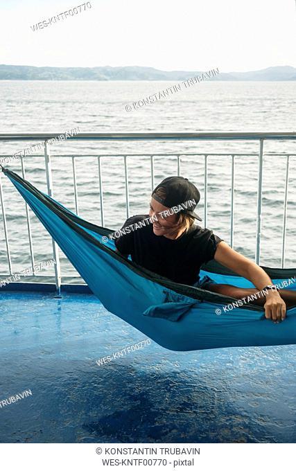 Indonesia, Lombok island, smiling woman in hammock on ship deck