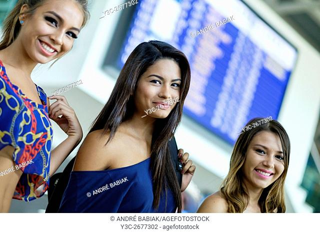 Three young females smiling at camera in front of an arrival departure time table display at an airport