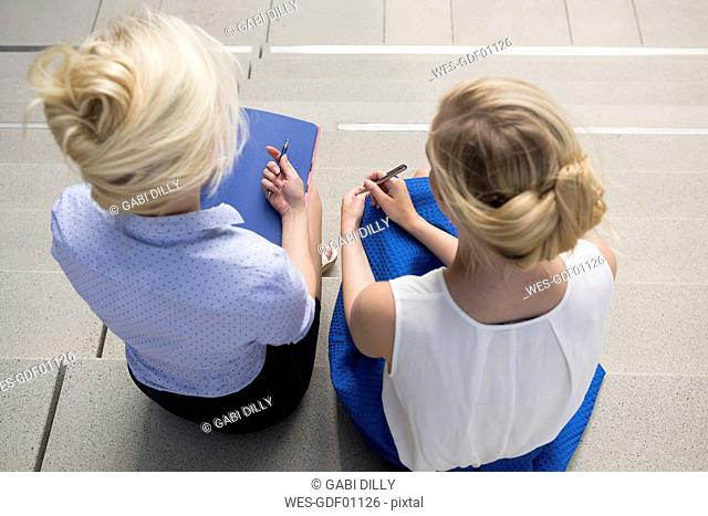 Two blond businesswomen with file and pens sitting on stairs, top view
