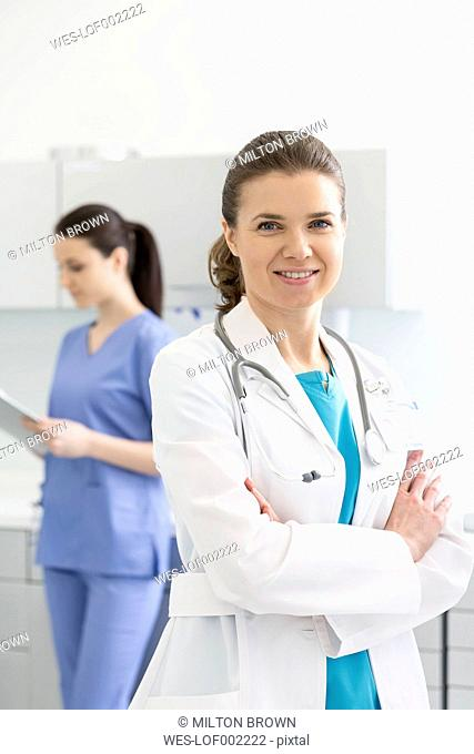 Portrait of doctor with nurse in background