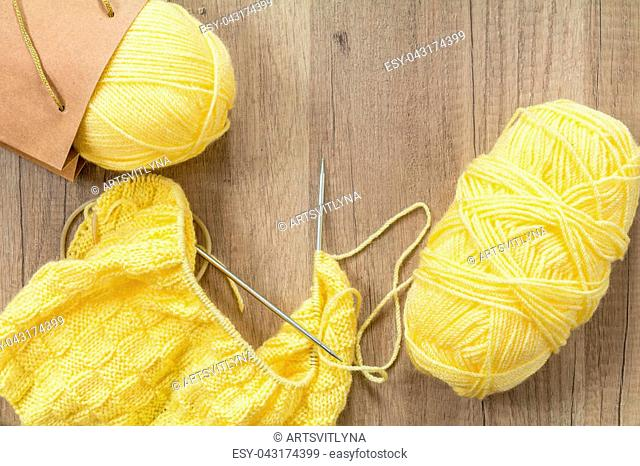 Light yellow knitting wool and knitting needles on wooden background. Top view.copy space. Knitted fabric and yarn on a wooden surface