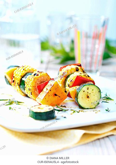 Vegetarian kebabs with courgettes, sweet corn on the cob, red pepper, butternut squash and drizzled olive oil