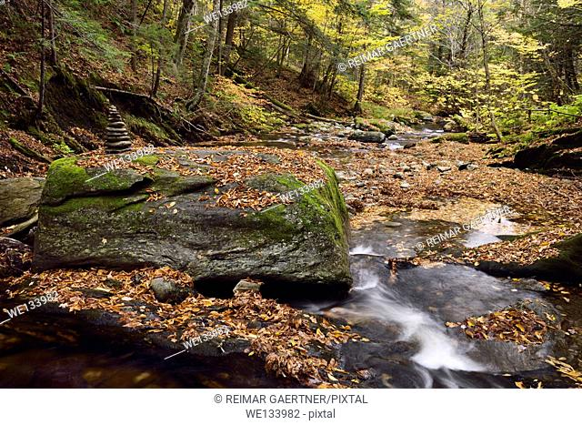 Stacked rocks at Sterling Brook below the Falls with boulders and Fall foliage north of Stowe Vermont