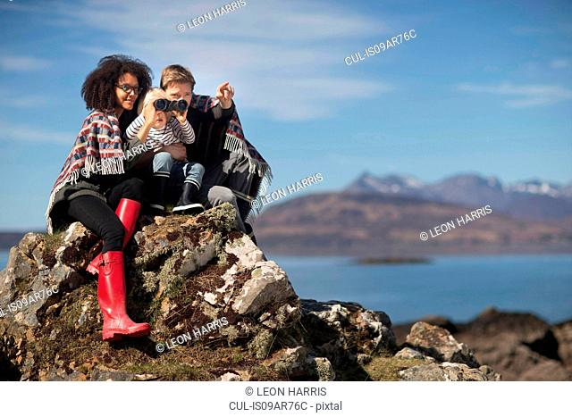 Family sitting on rocks, boy using binoculars