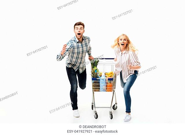 Full length portrait of a shocked couple running with a supermarket trolley isolated over white background