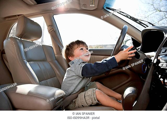 Little boy pretending to drive car