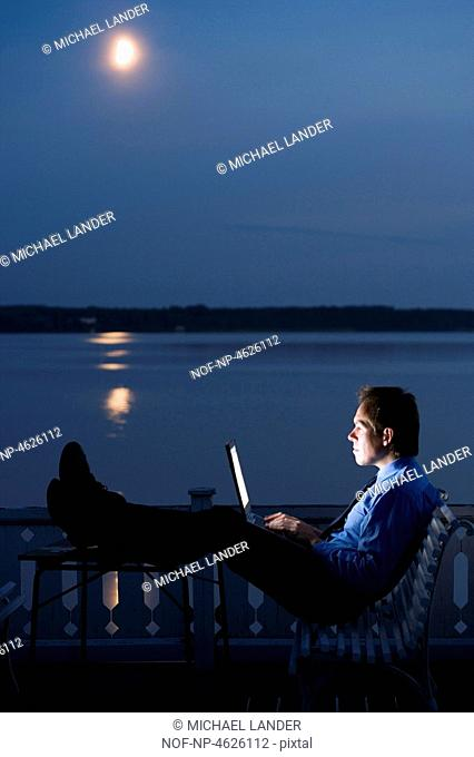 A man sitting with his laptop by waterfront at night