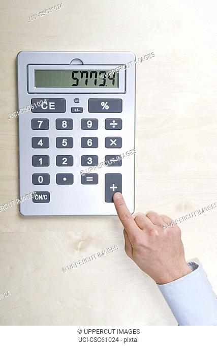 Businessman touching calculator button