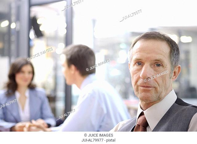 Senior businessman with coworkers in background