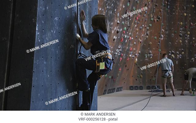 child crack climbing a wall in an indoor climbing gym