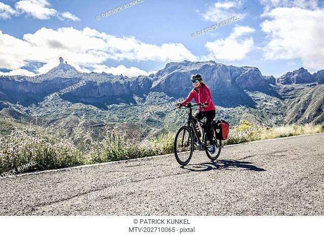 Woman riding electric bicycle on mountain road