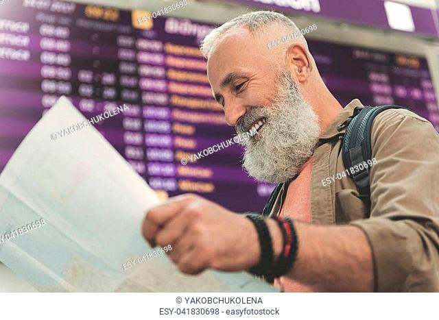 Low angle side view cheerful unshaven pensioner watching at map near board with information and smiling