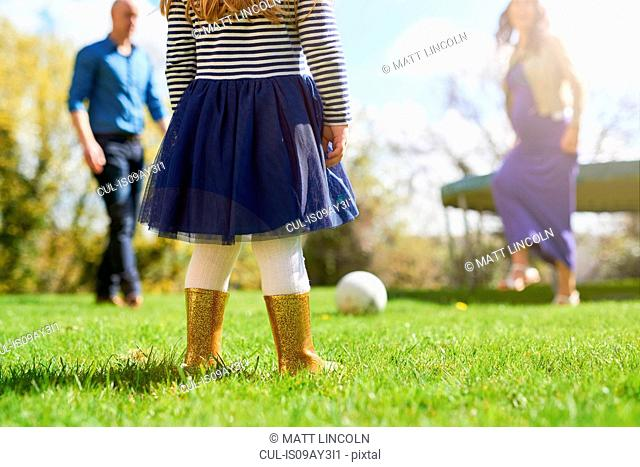 Low section of girl in garden with family playing with football