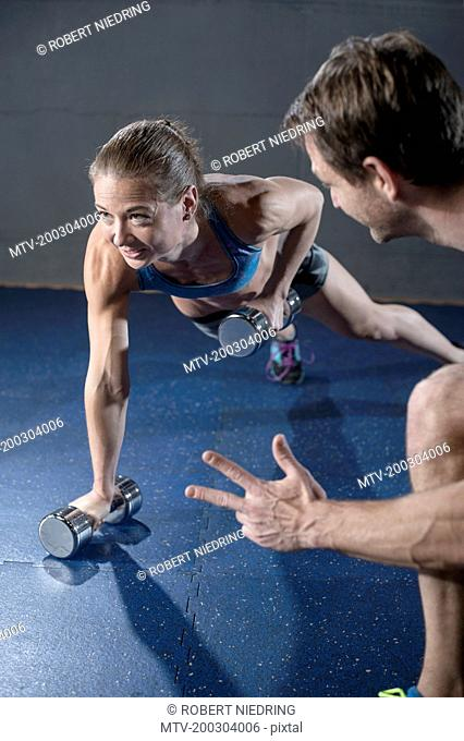 Fitness manager giving training to client in fitness studio, Bavaria, Germany