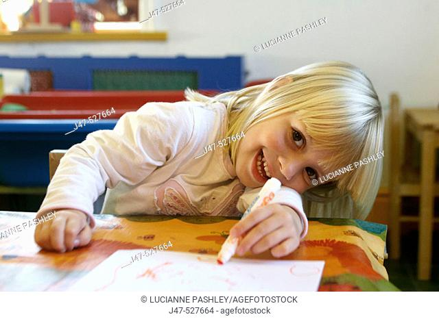 4 year old girl smiling into camera at nursery,drawing