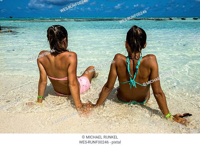 Carribean, Colombia, San Andres, El Acuario, rear view of two women sitting in shallow water
