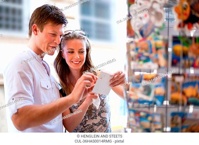 Smiling couple examining postcards