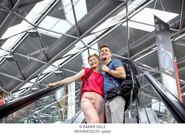 Happy couple on escalator at the airport