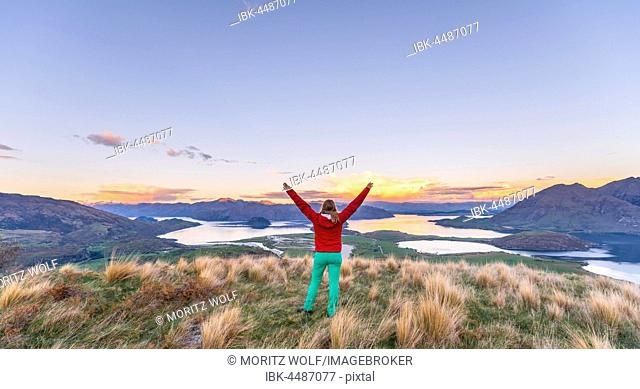 Hiker with arms spread out in the air, view of Lake Wanaka and mountains, sunset, Rocky Peak, Glendhu Bay, Otago, Southland, New Zealand