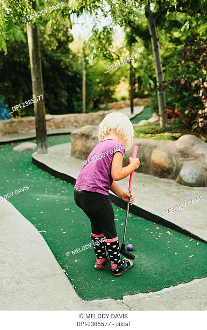 A young girl playing miniature golf; Peachland, British Columbia, Canada