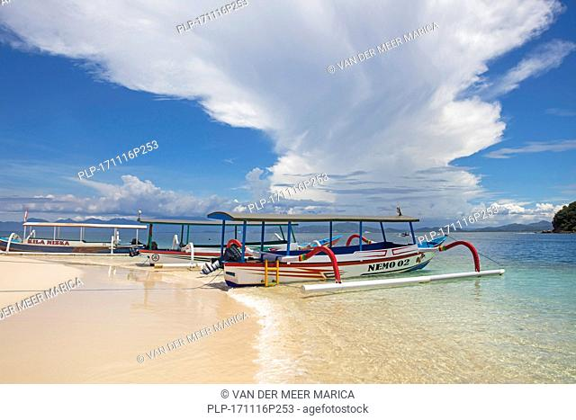 Outrigger tourist boats on idyllic tropical beach of the islet Gili Nanggu, part of the Gili Islands, island Lombok, Lesser Sunda Islands, Indonesia