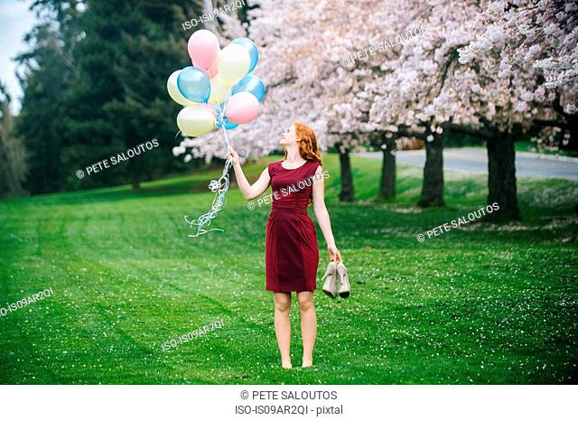 Young woman holding bunch of balloons in spring park