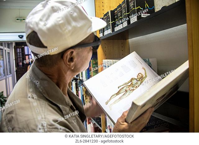 The famous national library of Fort de France in Martinique. retired caucasian man bold looking and pointing at an open book with anatomy and at all the books...