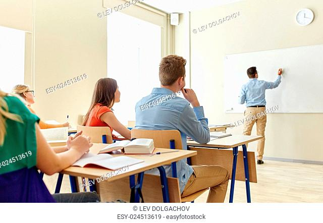 education, high school, learning, teaching and people concept - teacher standing in front of students and writing something on white board in classroom