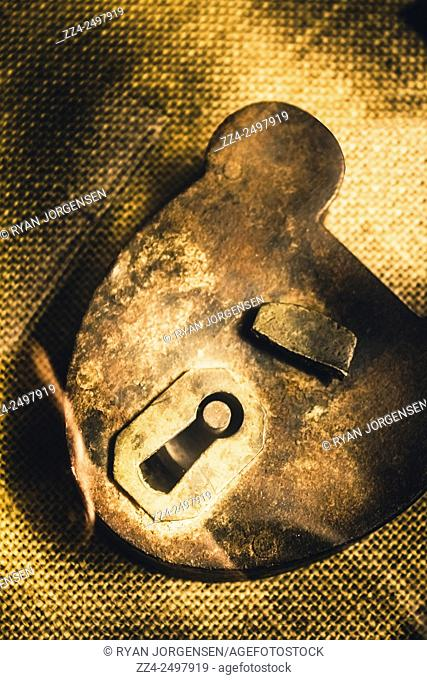 Vintage broken padlock lay open on a grungy thatched prison doormat. Jail break
