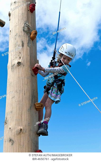 Little girls climbing in climbing equipment with leash and helmet at the climbing tower, Kronplatz, Corones, Puster Valley, South Tyrol, Italy