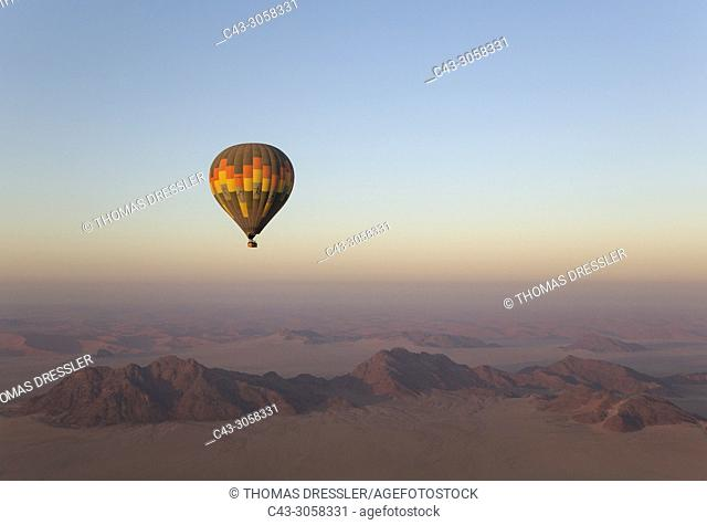 The hot-air balloon above an arid plain and isolated mountain ridges at the edge of the Namib Desert. Aerial view from a second balloon