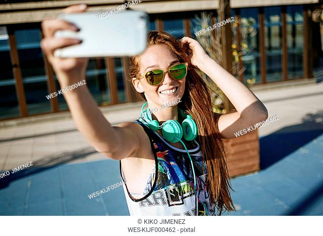 Smiling young woman wearing mirrored sunglasses taking selfie with smartphone