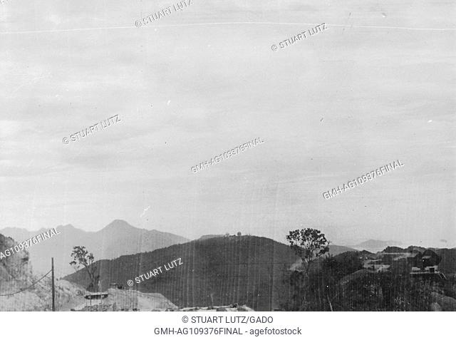 A few buildings and roads dot this mountainous landscape, Vietnam, 1966