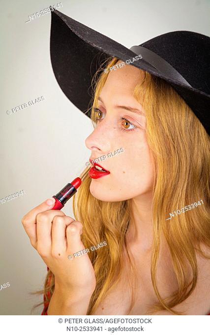 Blonde teenage girl applying lipstick