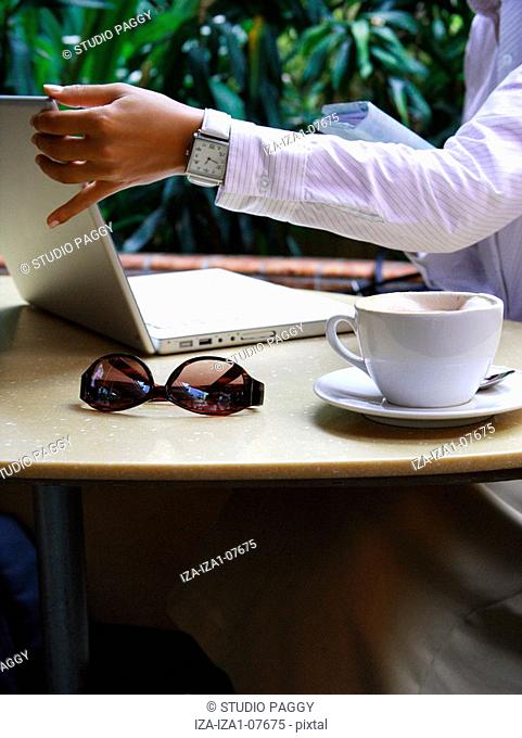 Close-up of a coffee cup with a businesswoman using a laptop