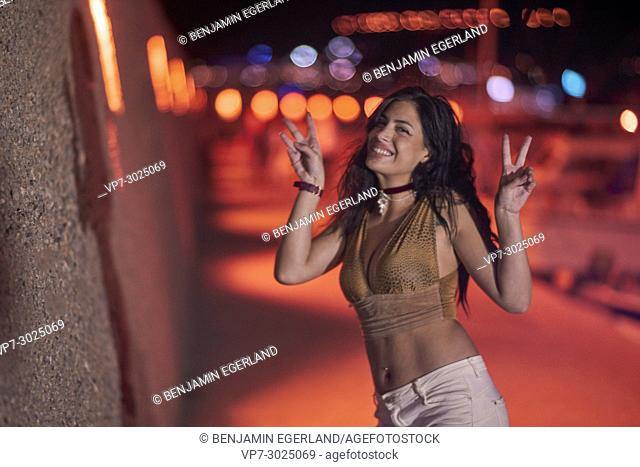 cheerful woman has fun in color lights of nightlife. Greek ethnicity. In Hersonissos, Crete, Greece