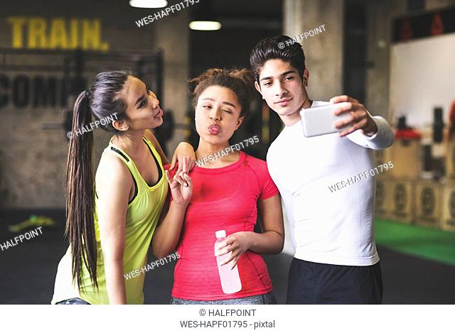 Three playful young people taking a selfie in gym