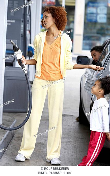 Black mother using pump at gas station