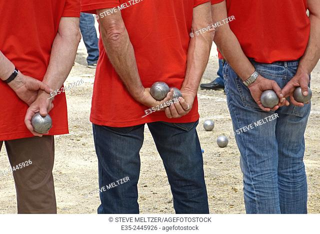 A team of petanque players watch their competition take its turn