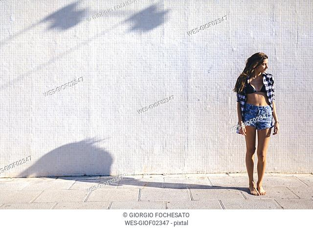 Young pretty woman wearing beach wear standing in front of white wall