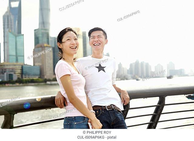 Tourist couple leaning against bridge railing, The Bund, Shanghai, China
