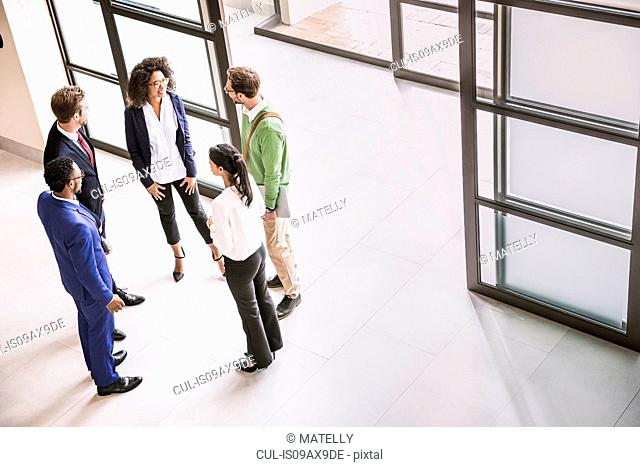 High angle view of businessmen and women having discussion at office entrance