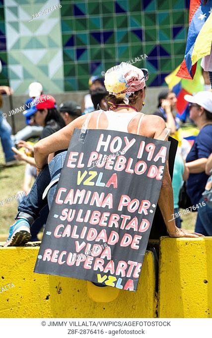 A woman holds a sign on her back, which says, today April 19, Venezuela walks by her freedom. Great march of the opposition against the coup