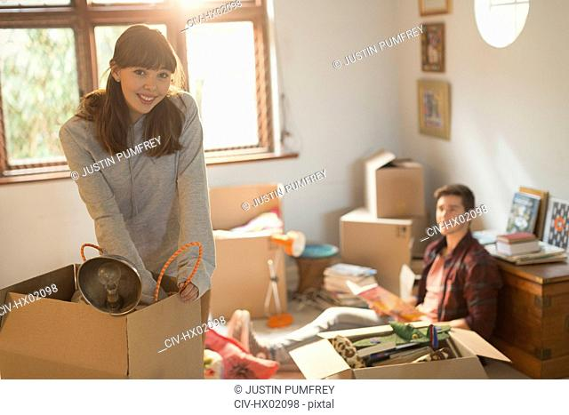 Portrait smiling young couple unpacking moving boxes in apartment