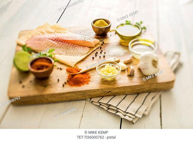 Raw tilapia and ingredients on cutting board